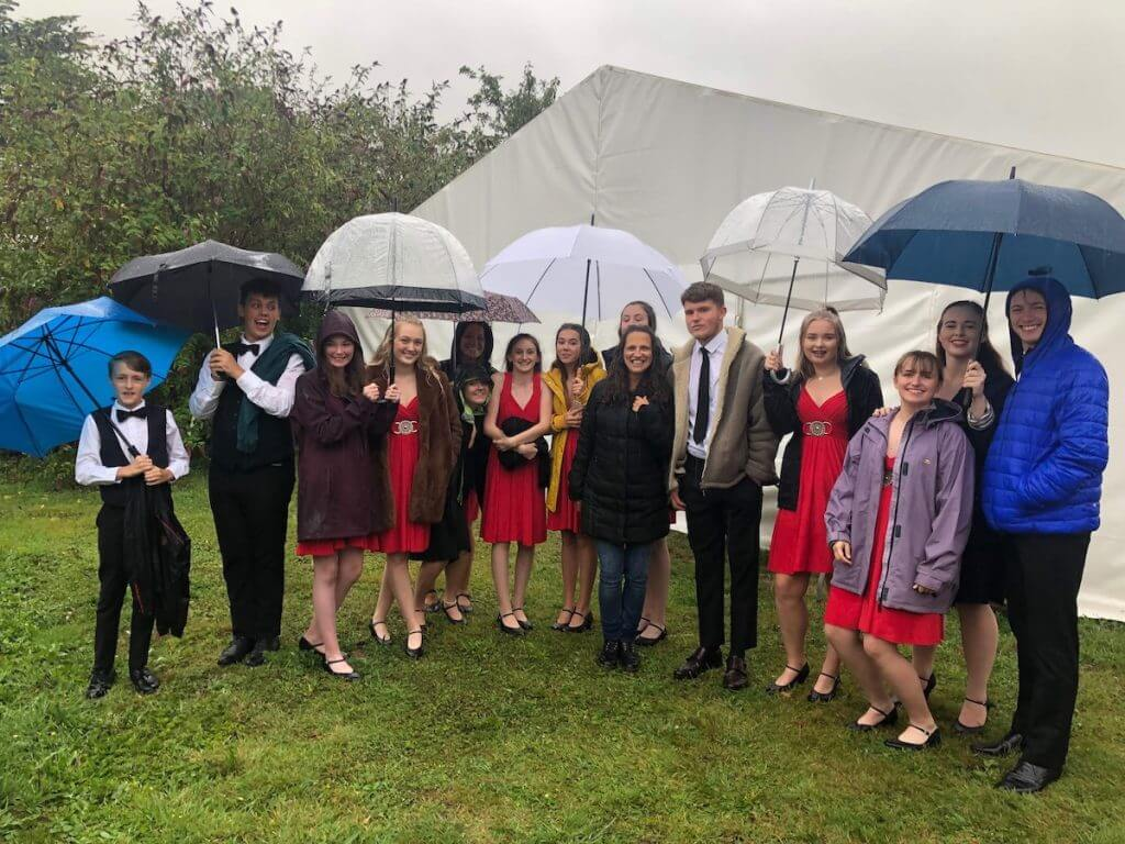 Group waiting in the rain outside the wedding marquee.